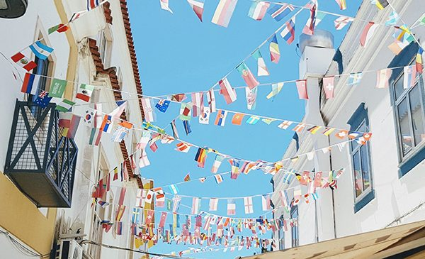 Various small international flags hang between buildings above a street. Public domain image.