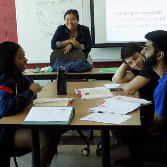 A Latina instructor with a stands over a small mixed gender, diverse group of UIC students