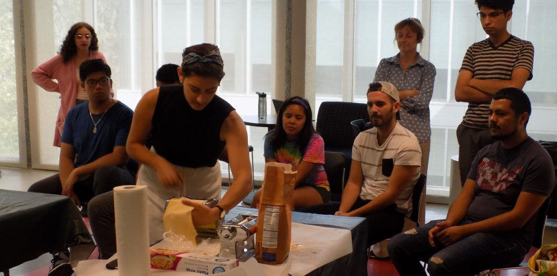 a female UIC faculty member demonstrates how to roll pasta to a mixed group of seated students