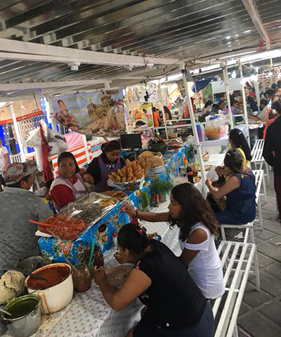 a group of Latina students eats at an outdoor market in Oaxaca
