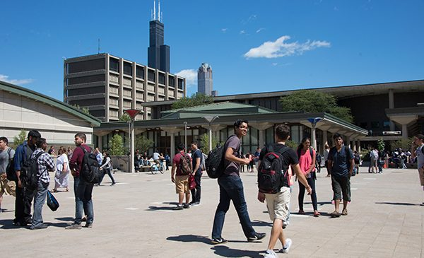 students walk across the UIC quad with the Sears Tower in the background