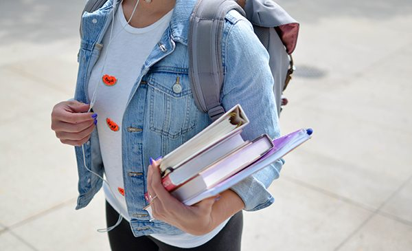 a female student in a denim jacket carrying a backpack holds a stack of books